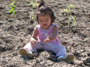Little girl sitting in garden