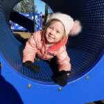 A child in a piece of playground equipment, wearing a winter coat and hat.