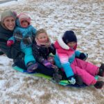 A women and three children sitting on a sled on the snow covered ground.