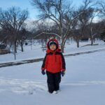 A child standing outside in a park with snow on the ground.