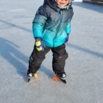 Child skating on a outdoor ice rink.