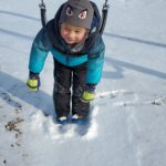 A child hanging on a swing outdoors during the winter.