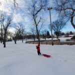 A child outdoors in a park pulling a slide on the snow.