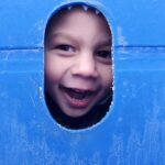 A child sticking his head through a hole in a piece of playground equipment.