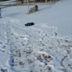 A child rolling down a snow covered hill.