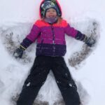 A child creating a snow angel on the ground.