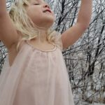 A child with a pink dress standing outside in the snow.