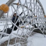 A child on a piece of playground equipment covered in frost.
