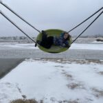 A child on a swing outdoors in the winter.