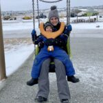 A women and child on a swing outdoors during the winter.