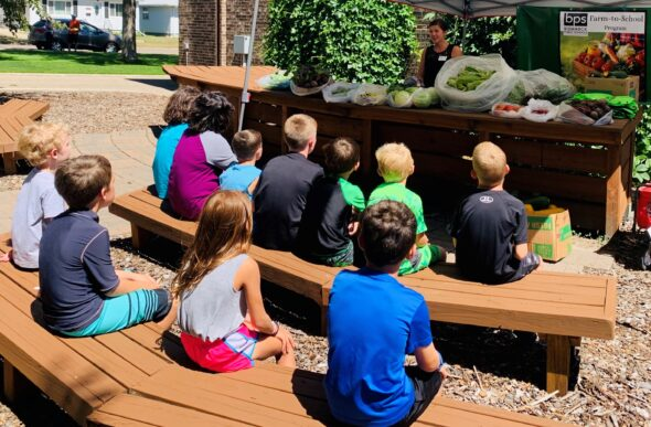 kids sitting on benches, learning about local produce