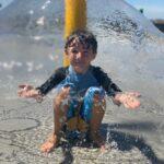 boy under water feature at splash pad